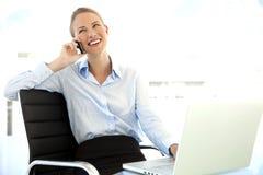 Empresaria en el teléfono en el lugar de trabajo Imagen de archivo libre de regalías