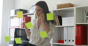 Empresaria en la blusa blanca que considera etiquetas engomadas sobre el vidrio y que habla en el teléfono almacen de metraje de vídeo