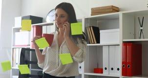 Empresaria en la blusa blanca que considera etiquetas engomadas sobre el vidrio y que habla en el teléfono metrajes