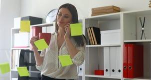 Empresaria en la blusa blanca que considera notas pegajosas sobre el vidrio y que habla en el teléfono almacen de video