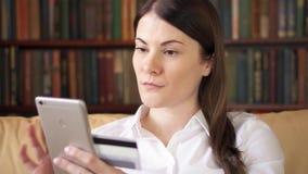 Empresaria en la camisa blanca que se sienta en el sofá en sala de estar que compra en línea con la tarjeta de crédito en móvil almacen de video