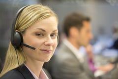 Empresaria en la oficina en el teléfono con las auriculares, mirando c Imagen de archivo
