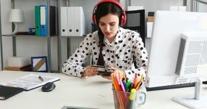 Empresaria en los auriculares rojos que incorporan el número de tarjeta de crédito en smartphone almacen de metraje de vídeo