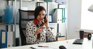 Empresaria en los auriculares rojos que sostienen la tarjeta de crédito y que hablan en smartphone almacen de video