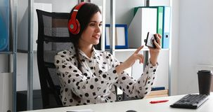 Empresaria en los auriculares rojos que tiran el vídeo en smartphone en oficina moderna almacen de metraje de vídeo