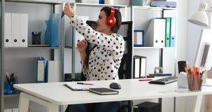 Empresaria en los auriculares rojos que tiran el vídeo en smartphone en oficina moderna almacen de video