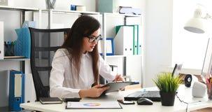 Empresaria en los vidrios negros que llenan documentos y que trabajan en el ordenador portátil en oficina moderna almacen de metraje de vídeo