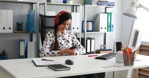 Empresaria en música de los auriculares rojos y smartphone con que escuchan metrajes
