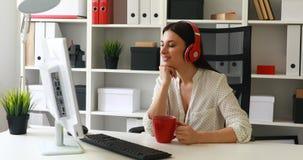 Empresaria en música que escucha de la blusa blanca y mirada al monitor almacen de metraje de vídeo