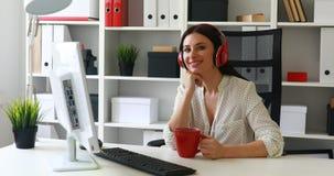 Empresaria en música que escucha de la blusa blanca y mirada al monitor almacen de video