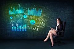 Empresaria en oficina con la tableta a disposición y el gráfico de alta tecnología Imagen de archivo libre de regalías