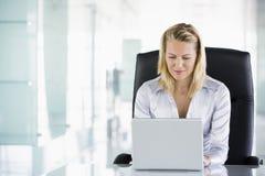 Empresaria en oficina usando la computadora portátil foto de archivo libre de regalías