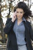 Empresaria en un parque que habla el teléfono móvil. Fotos de archivo libres de regalías