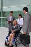 Empresaria en un sillón de ruedas con los colegas Imagen de archivo libre de regalías