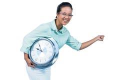 Empresaria encantada que sostiene un reloj Imagen de archivo