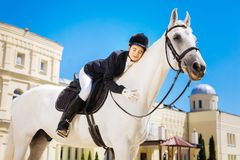 Empresaria encariñada con el equestrianism que abraza su caballo blanco foto de archivo