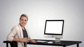 Empresaria enfocada confiada que habla con la cámara y que mira para supervisar cerca de ella en fondo de la pendiente almacen de video