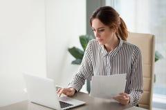 Empresaria enfocada seria que mecanografía en el ordenador portátil que sostiene los papeles que preparan informe imagenes de archivo
