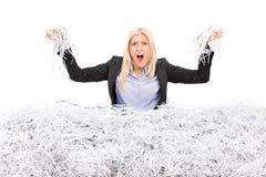 Empresaria enojada en una pila de papel destrozado Fotos de archivo libres de regalías