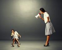 Empresaria enojada que grita en la mujer perezosa imagen de archivo