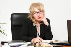 Empresaria envejecida centro, en el escritorio Fotos de archivo