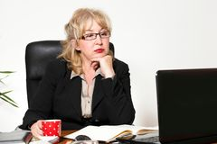 Empresaria envejecida centro, en el escritorio Fotografía de archivo libre de regalías