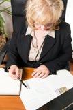 Empresaria envejecida centro, escribiendo el documento Foto de archivo libre de regalías