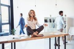 Empresaria envejecida que se sienta en la tabla y que medita en la posición de loto mientras que colegas que trabajan detrás Foto de archivo