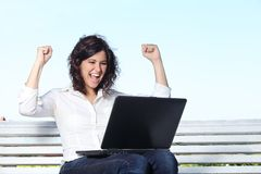 Empresaria eufórica con un ordenador portátil que se sienta en un banco Fotografía de archivo libre de regalías