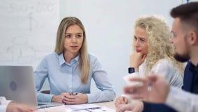 Empresaria europea acertada que habla y que discute el trabajo teniendo reunión del equipo almacen de video