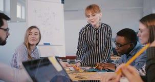 Empresaria europea confiada joven atractiva pronunciar discurso al equipo multiétnico en la reunión moderna del personal del lu almacen de metraje de vídeo
