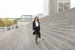 Empresaria europea que se coloca en las escaleras con el bolso y los altos edificios en fondo Fotos de archivo libres de regalías