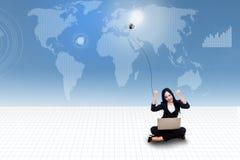 Empresaria feliz con el ordenador portátil y bombilla en mapa del mundo azul Fotografía de archivo