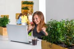 Empresaria feliz emocionada con los brazos aumentados que se sientan en la tabla con el ordenador portátil que celebra su éxito C Fotografía de archivo libre de regalías