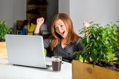 Empresaria feliz emocionada con los brazos aumentados que se sientan en la tabla con el ordenador portátil que celebra su éxito C Fotografía de archivo