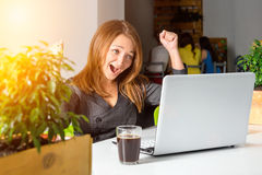 Empresaria feliz emocionada con los brazos aumentados que se sientan en la tabla con el ordenador portátil que celebra su éxito C Imagenes de archivo