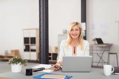 Empresaria feliz en su tabla con el ordenador portátil Fotos de archivo libres de regalías