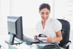 Empresaria feliz que arregla su orden del día en su escritorio Imágenes de archivo libres de regalías