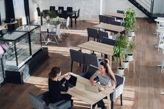Empresaria feliz que habla con la empresaria en oficina Dos mujeres que se sientan en la tabla con los ordenadores portátiles y e imágenes de archivo libres de regalías