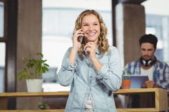 Empresaria feliz que habla sobre el teléfono en oficina Imagen de archivo libre de regalías