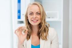 Empresaria feliz que muestra la muestra aceptable en la oficina Imagen de archivo libre de regalías