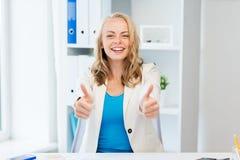 Empresaria feliz que muestra los pulgares para arriba en la oficina Imagen de archivo libre de regalías
