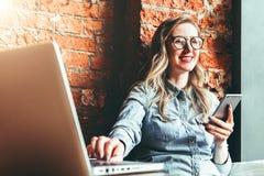 Empresaria feliz que se sienta en cafetería en la tabla, usando smartphone, onlaptop de trabajo El frillancer de la muchacha trab foto de archivo