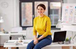 Empresaria feliz que se sienta en el escritorio en la oficina imagen de archivo