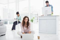 Empresaria feliz que se sienta en el piso usando el ordenador portátil Imágenes de archivo libres de regalías