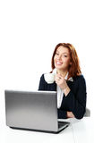 Empresaria feliz que se sienta en la tabla con el ordenador portátil y el café de consumición Fotografía de archivo