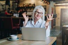 Empresaria feliz que se sienta en la tabla delante del ordenador portátil, llevando a cabo las manos ascendentes y sonriendo, tra Fotos de archivo