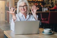 Empresaria feliz que se sienta en la tabla delante del ordenador portátil, llevando a cabo las manos ascendentes y sonriendo, tra Fotografía de archivo libre de regalías