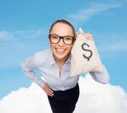 Empresaria feliz que sostiene el bolso del dinero con el dólar Foto de archivo