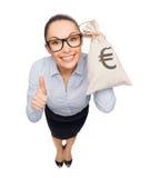 Empresaria feliz que sostiene el bolso del dinero con euro Fotografía de archivo libre de regalías